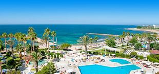Adults only resort met palmbomen, zwembad en de zee op Cyprus