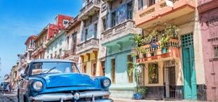 Gekleurde huizen en blauwe auto Cuba