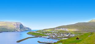 De haven en het groene landschap op de Faeröer eilanden, Denemarken