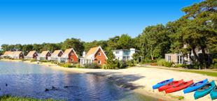 Vakantiehuisjes op een rij aan het water van Droomparken De Zanding