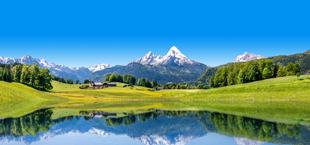 Besneeuwde bergtoppen en groene graslanden in Duitsland, met een weerspiegeling in het water
