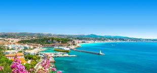 De haven van Nice, Frankrijk met een turquoise zee en paarse bloemen op de voorgrond