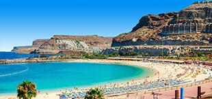 Helderblauwe zee met druk bezocht strand op Gran Canaria