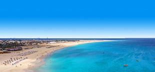 Helderblauwe zee met druk strand in Kaapverdië