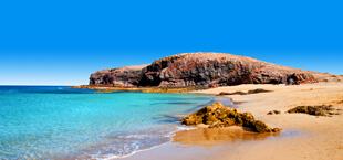 Helderblauwe zee met strand op Lanzarote