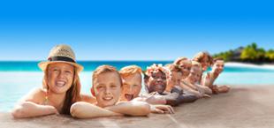 Blije kinderen in het zwembad met blauwe lucht