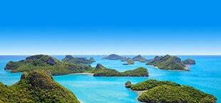 Helderblauwe zee met verschillende kleine bergen in Thailand