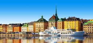 Huisjes aan het water dat weerspiegeld in Zweden