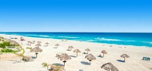 Ligbedden en parasols op het witte zandstrand bij Cancun in Mexico