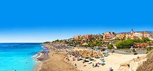Blauwe zee met klein strand en hotels op de achtergrond in Tenerife