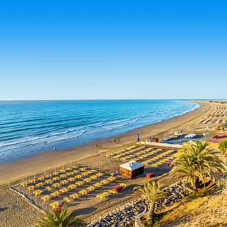 Vele ligbedjes en parasols op het strand van Playa del Ingles in Gran Canaria