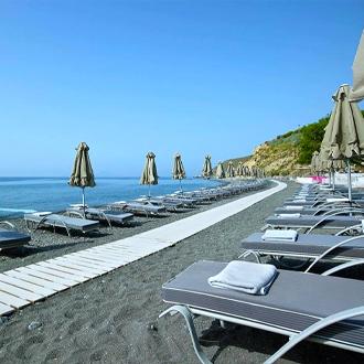 Ligbedden en parasols op het strand van Agios Fokas, Kos