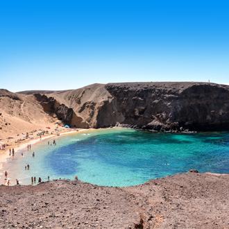 Baai met rotsen en helderblauwe zee in Playa Blanca op het Spaanse eiland Lanzarote