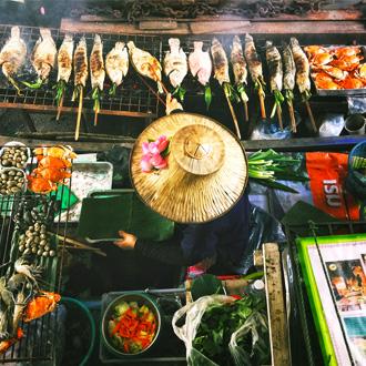 Vrouw is verse vis aan het bereiden in Bangkok