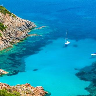 Blauwe baai met heldere zee en rotsen