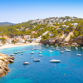 Boten op het blauwe water in Cala Vadella Ibiza