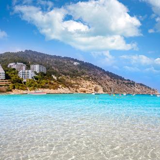 Uitzicht op helderblauw water, een berg en huizen in Calla Llonga, Ibiza