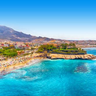 Baai met blauwe zee met een berg en huizen Costa Adeje