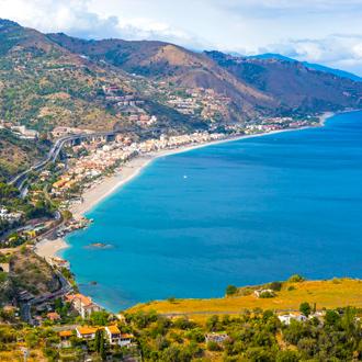 De kustlijn van Giardini Naxos, met een azuurblauwe zee en groene bergen