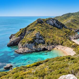 Het strand en helderblauwe zee in Agios Georgios op het Griekse eiland Corfu