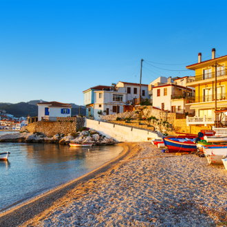 Uitzicht op huisjes, het strand en vissersboten in Kokkari op Samos