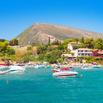 Panorama Agios Sostis met blauwe zee, bootjes en bergen