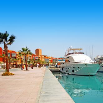 Boulevard met oranje gebouwen, een boot en palmbomen Hurghada