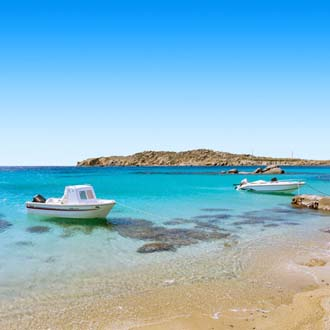Helderblauwe zee met boot aan de kust van Mykonos, Griekenland