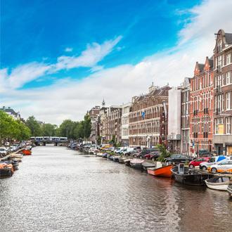 Het kanaal met bootjes en huizen in Amsterdam
