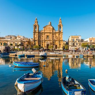 Vissersbootjes in de haven van Sliema met de kerk op de achtergrond