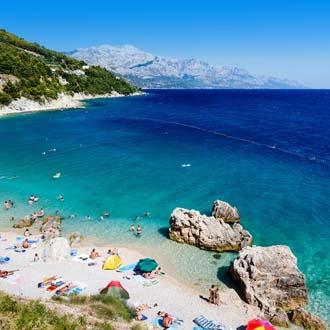 Levendig strandje, met zee in Midden-dalmatie