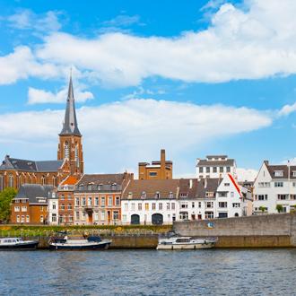 De maas is Maastricht met uitzicht op gebouwen en bootjes in Nederland