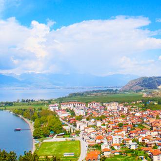 De kust van Ohrid in Macedonie met natuurlandschap en huizen met oranje daken