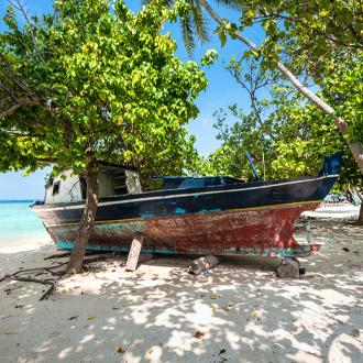 Oud bootje op het strand van Gulhi eiland Zuid Male Atol