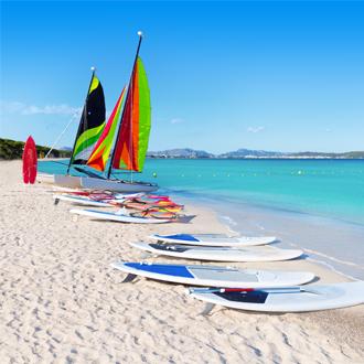 Strand van Platja de Muro met windsurf boards en blauwe zee in Alcudia
