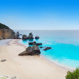 Uitzicht op zandstrand, rotsen en helderblauw water in Portugal