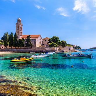 Prachtige foto van een kerkje met een haventje op de voorgrond in Hvar, Kroatië