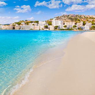 Santa Ponsa azuurblauwe zee met wit strand en bergen met huisen in de verte