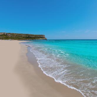 Zandstrand met azuurblauwe zee in Son Bou