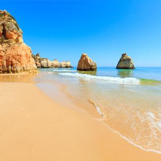 Het strand van Alvor met rotsblokken in de Algarve, Portugal