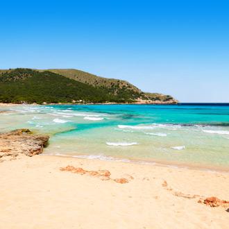 Het strand van Cala Ratjada met uitzicht op de zee en een berg op Mallorca