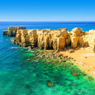 Strand van Portimao met gele rotsen en blauwe zee