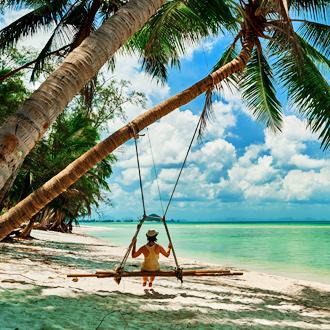 Persoon op een schommel aan een palmboom op Koh Samui