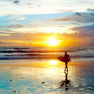 Surfer bij zonsondergang in Kuta