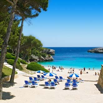 Zandstrand met ligbedden Cala d'Or Mallorca in blauwe baai