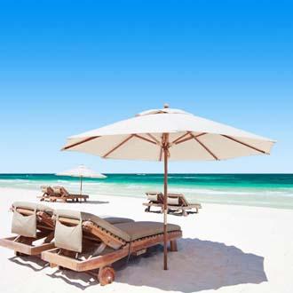 Ligbedjes en een parasol op het witte zandstrand bij Playa del Carmen in Mexico
