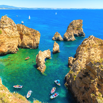 Rotsblokken in azuurblauw zeewater en vissersboten in Alvor in Portugal