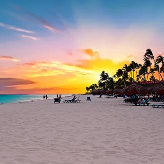 Zonsondergang bij Druif Beach op het witte zandstrand met palmbomen op de achtergrond op Aruba