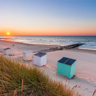 Het strand met strandhuisjes bij zonsondergang in Zoutelande
