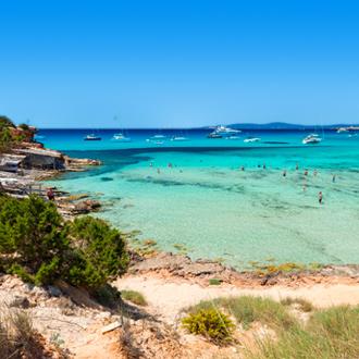 Het strand Cala Saona met kristalhelder water